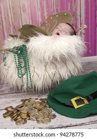 Beautiful one week old newborn sleeping with wings beautiful Irish Fairy Princess. The leprechaun has left behind his gold coins and hat.