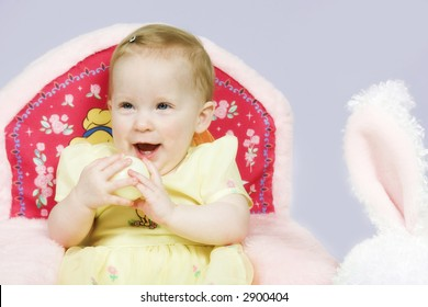 Beautiful one year old baby girl plays with easter egg