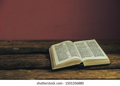 Beautiful open Holy Bible on old oak wooden table and dark red wall background. Religious concept.