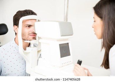 Beautiful optician wearing labcoat with non-contact tonometer checking handsome patient intraocular pressure at optic store
