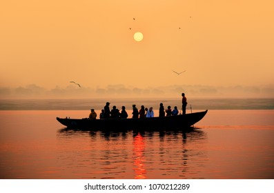 Beautiful orange colored sunset on a Ganges river with a silhouette of a boat and people.