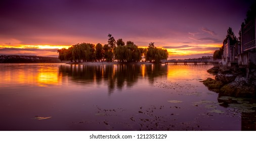 beautiful orange and purple sunset over a beautiful little island on the lake