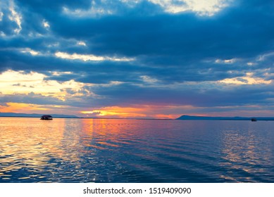 Beautiful Orange and red dramatic colors of sunset and cirrus clouds above the sea. Sky blue and orange natural dawn composition over the sea, Warm colors with pontoon. Aerial view.