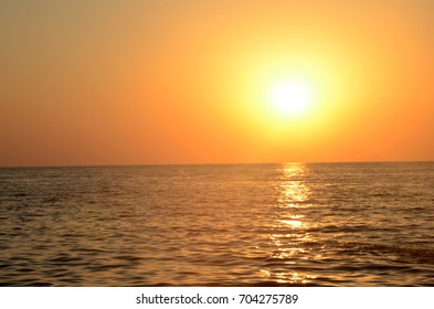 Beautiful orange sunset and blue sky over the sea with waves
