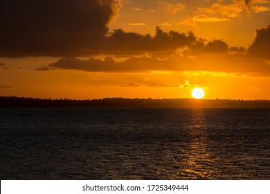 A beautiful orange sunset catching the sun as an orange ball just before it dips below the horizon.