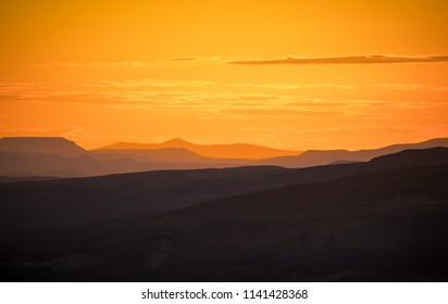 Beautiful orange sunset with clouds over mountain landscape (Kamchatka peninsula)