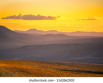 Beautiful orange sunset with clouds over mountain landscape and meadow (Kamchatka penisula)