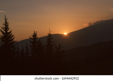 Beautiful orange Sunset in mountains. Trip with camping. the sun sets behind the mountain.