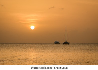 A beautiful orange sunset on Seven Mile Beach in Grand Cayman with boats on the horizon.