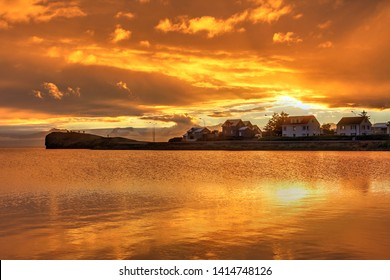 A beautiful orange sunset shortly after a storm in the small fishing village of Hofn in South-Eastern Iceland.