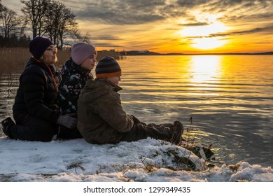 Beautiful orange winter landscape by the sea with a woman and children sitting in the snow on a rock looking at a bright sunset reflecting in the water.