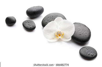 Beautiful orchid flower with stones on white background