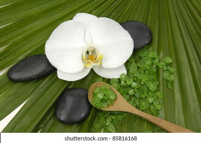 Beautiful orchid with zen stones with green bath salts in spoon on palm leaf background