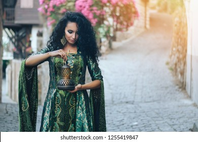 Beautiful oriental girl with a lamp in hand. Portrait of an arab female model. Hookah, tradition, east, asia concept.