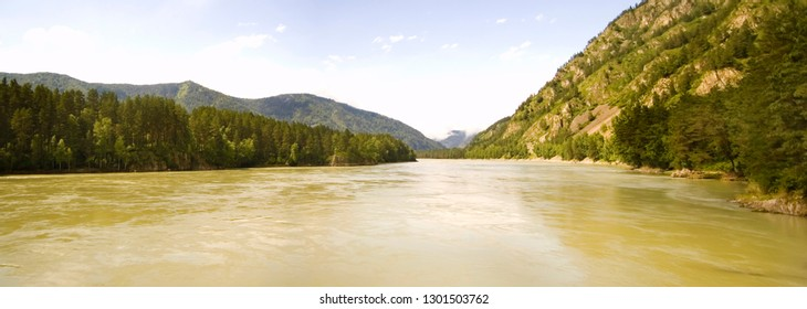 Beautiful and original panorama. Beautiful and majestic landscape and panorama of mountain and wild rivers with muddy water against the backdrop of mountains, forests and the sky is clean.