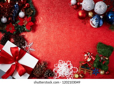 Beautiful ornaments Christmas holiday abstract background toys and Red Gift Box with tree balls decorations on red background, Flat lay. Layout with free text space.