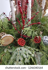 Beautiful outdoor Christmas floral arrangement in a planter with evergreen and pine branches, a shiny silver ornament, wood decorations, berries, and birch trees in the background.