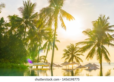 Beautiful outdoor tropical nature landscape of swimming pool in hotel resort with coconut palm tree umbrella and chair nearly sea ocean beach at sunrise time