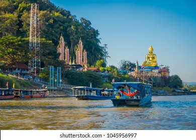 Beautiful outdoor view of a group of tourists in tourist boats visiting the golden budha located at golden triangle Laos