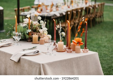 Beautiful outdoor wedding decoration in city. Candles, dried flowers and accessories, bouquets and glasses on table with linen tablecloth on newlywed table on green lawn, flat lay, free space, nobody