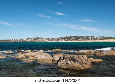 Beautiful outlook on Curl Curl beach seen from the North end with rocks and water in the foreground - NSW / Australia