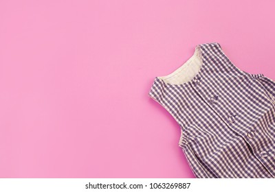 Beautiful overalls for a newborn baby on a pink background, top view. Baby clothes.