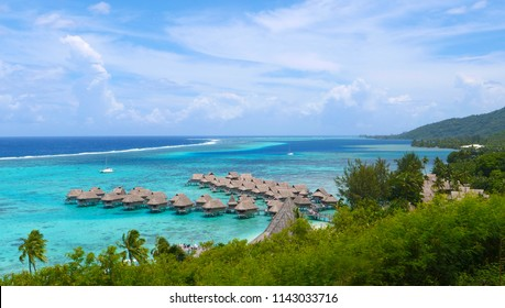 Beautiful overwater villas in stunning lagoon overlooking tropical sunny island. Luxury resort with oceanfront bungalows sitting in emerald ocean bay on exotic island. Luxury seaside vacation rentals