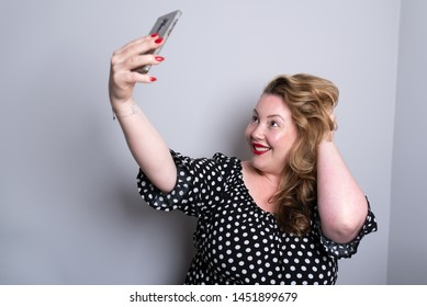 Beautiful overweight plus size model taking selfies for social media with her smart phone. the woman is touching her hair and wearing a dotted dress