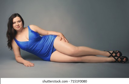 Beautiful overweight woman in blue swimsuit on grey background