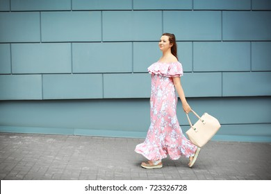 Beautiful overweight woman in pink ruffled dress walking on city street