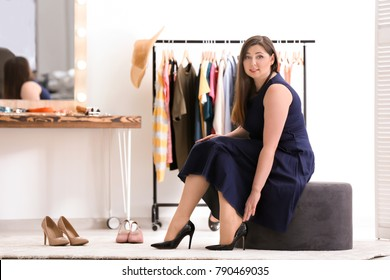 Beautiful overweight woman trying on shoes in boutique