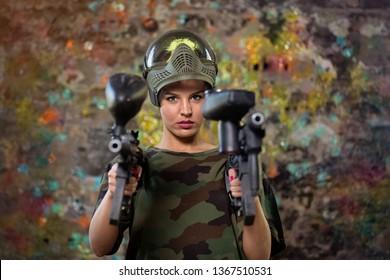Beautiful paintball girl with guns