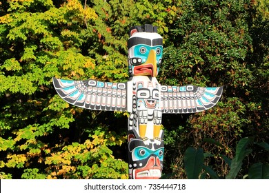 Beautiful painted colorful totem pole top detail - eagle's head with spread wings and the monkey, made by indigenous / native people of Canada, in Stanley park, Vancouver BC, October 15, 2017