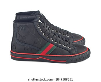 Beautiful pair of ultra fashionable gucci sneakers made of black fabric with the company logo, isolated on a white background with a shadow. Side view. Belarus, Minsk, 21.10.2020.