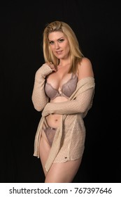 Beautiful pale blonde in mauve lingerie and a beige sweater