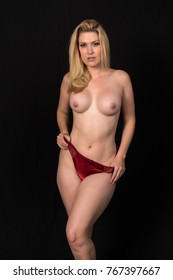 Beautiful pale blonde standing topless in red panties