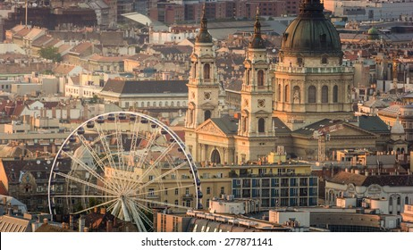 Beautiful Panorama Aerial view of St. Stephen's Basilica Big dome above sunny buildings, Ferris wheel and rooftops under Golden Sunset at Dusk in Summer evening, Budapest