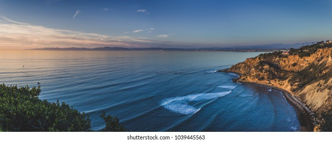 Beautiful panorama of the giant bluffs and homes of Flat Rock Point at sunset with coastline view of nearby South Bay beach cities in the background, Palos Verdes Estates, California