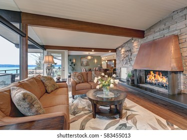 Beautiful panorama house interior features great room with white plank ceiling accented with wood beams over Cozy seating arrangement and Awesome fireplace stone wall. Northwest, USA