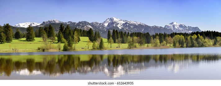 beautiful panorama landscape in Bavaria, Germany, with alps mountains mirroring in lake