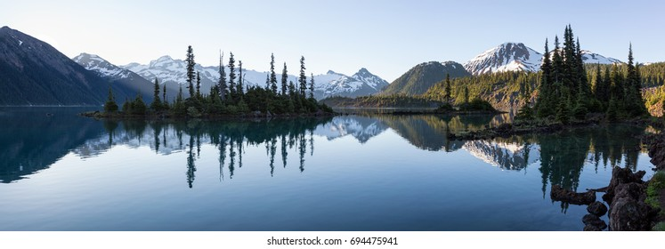 Beautiful panorama landscape at the Glacier Lake with rocky islands and mountains in the background. Taken in Garibaldi Lake, Near Whistler and Squamish, North of Vancouver, British Columbia, Canada.