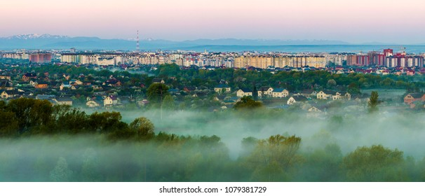 Beautiful panorama of morning aerial view of Ivano-Frankivsk city, Ukraine. Scene of quiet suburbs among green trees under dense fog and tall buildings on distant Carpathian mountains background.