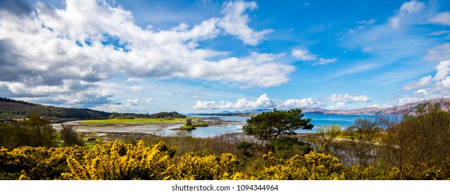 Beautiful panorama at Port Appin in the Highlands of Scotland, showing Loch Linnhe and Castle Stalker in springtime, with gorse in full flower.