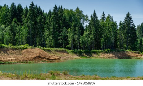 Beautiful panorama of quarry lake with emerald green water and big forest as background. Closed down quarry now is bathing place with great nature landscape. Theme for traveling and tourism