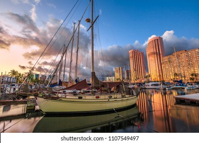 Beautiful panorama of sailing boats docked at the Ala Wai Harbor the largest yacht harbor of Hawaii and Honolulu skyline at sunset. On background, a luxurious hotel near Waikiki beach in Honolulu.