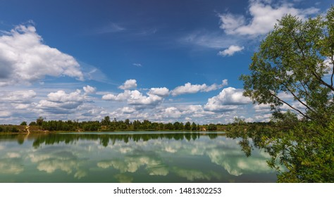 Beautiful panorama of sunny summer countryside landscape. Horizon line, green trees of forest, blue sky and reflection of white fluffy clouds in river water. Horizontal color photography.