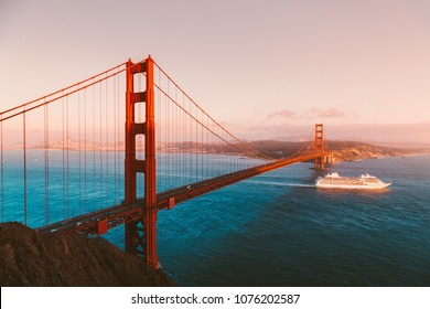 Beautiful panorama view of cruise ship passing famous Golden Gate Bridge with the skyline of San Francisco in the background in beautiful golden evening light at sunset in summer, California, USA