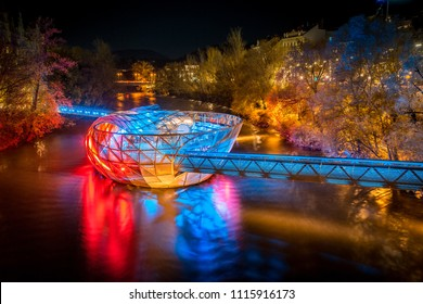 Beautiful panorama view of famous Grazer Murinsel, an artificial floating island in the middle of Mur river illuminated at night, Graz, Styria region, Austria