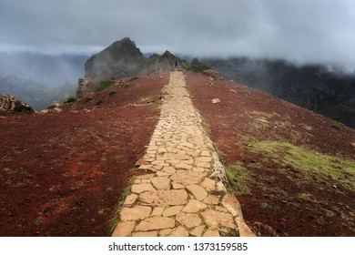 Beautiful panorama view of the footpath trail in the mountains of Madeira at Pico do Areeiro (Arieiro) while hiking to Pico Ruivo on a cloudy summer day with ominous storm weather