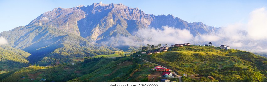Beautiful panorama view of rocky mountain range Mount Kinabalu with tropical landscape during morning with homestay and green vegetation at foreground. Mount Kinabalu view in Kundasang Sabah Malaysia.